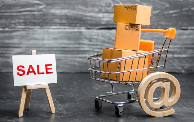Un carrito de la compra lleno de cajas de cartón y un caballete con la palabra venta y símbolo de correo electrónico