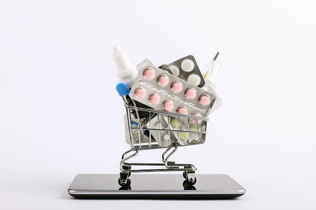 Carrito de la compra con medicamentos y pastillas está en el teléfono inteligente. concepto de venta online.