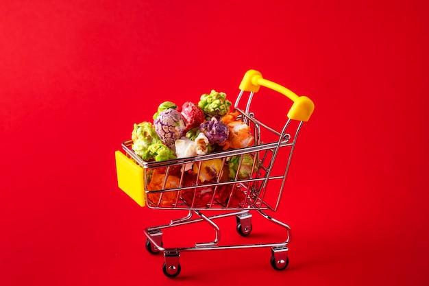 Carrito de la compra pequeño con palomitas de maíz de color en la pared roja