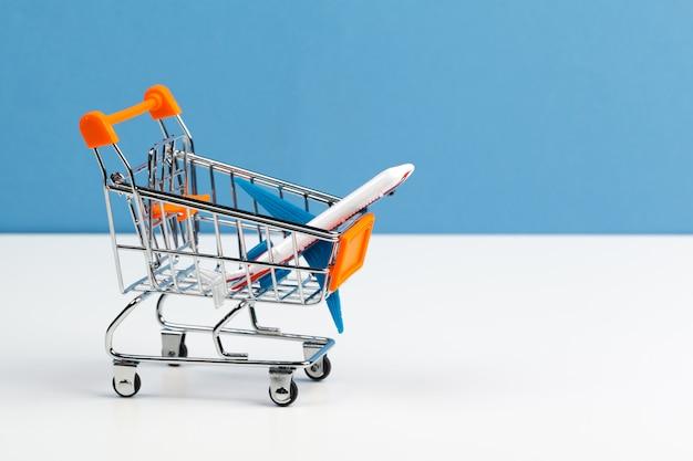 Carrito de compras con aviones de juguete en mesa blanca de cerca