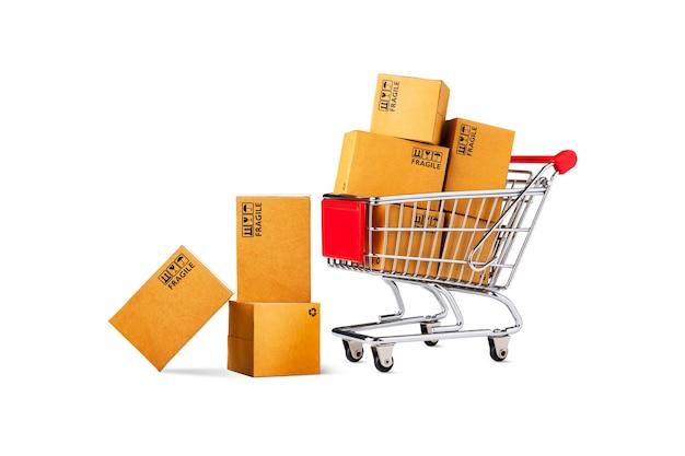 Carrito de compras y cajas de paquetes de productos aisladas sobre fondo blanco, tienda online y concepto de entrega