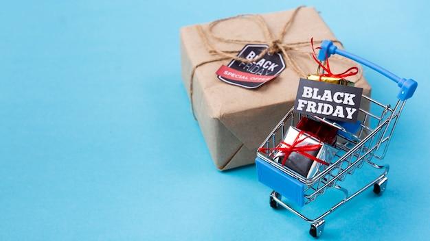 Carrito de compras cerca de regalo de viernes negro