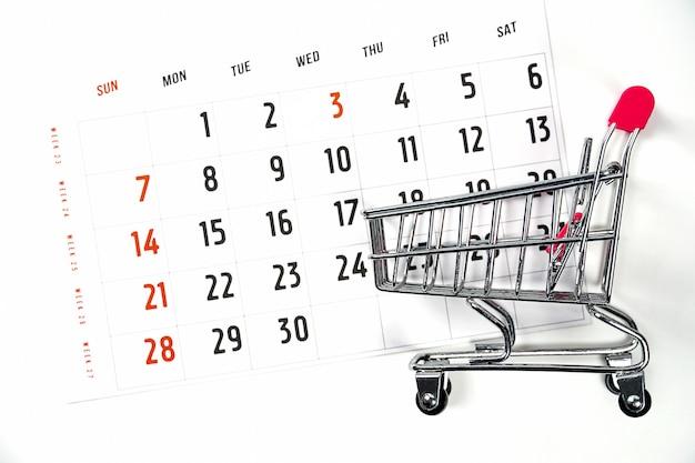 Carrito de compras en el fondo del calendario tiempo en el calendario para compras flatlay