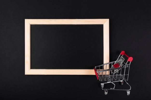 Carrito de compras frente a pizarra en blanco