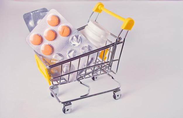 Carrito de compras de juguete con medicamentos: pastillas, blister, botellas médicas.