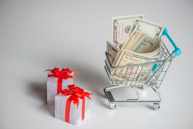Carrito de compras lleno de dinero y cajas de regalo de navidad.