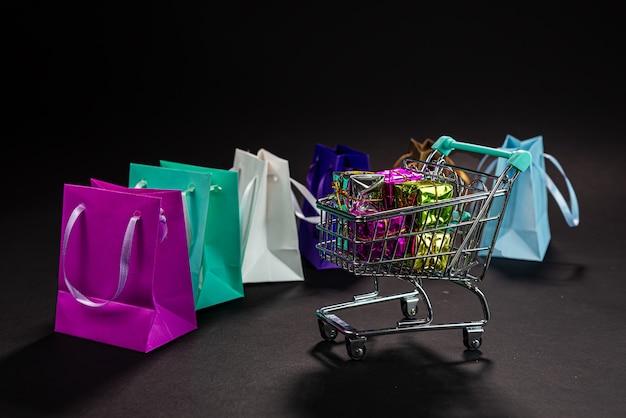 Carrito de compras de metal pequeño lleno de regalos, bolsas de colores, aislado en la oscuridad, compras en línea, venta de invierno, supermercado, promoción de descuento y concepto de viernes negro