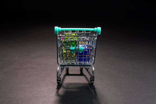 Carrito de compras de metal pequeño lleno de regalos coloridos, aislado en la oscuridad, compras en línea, venta de invierno, supermercado, promoción de descuento y concepto de viernes negro