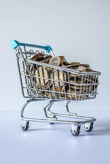 Carrito de compras en miniatura lleno de monedas