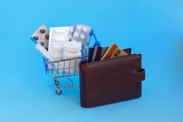 Un carrito de compras con pastillas y una jeringa junto a un bolso con tarjetas de crédito.