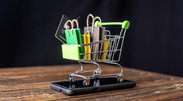 Carrito de compras pequeño con bolsas de papel y tarjeta de crédito en el interior y teléfono