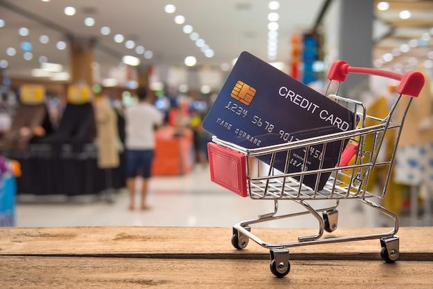 Carrito de compras pequeño con tarjeta de crédito dentro y detrás está borroso. tienda - concepto de crédito de uso para compras.