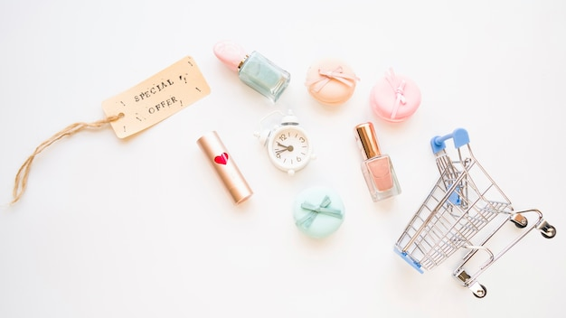 Carrito de compras con poco snooze, macarrones, etiqueta de venta, lápiz labial y esmalte de uñas