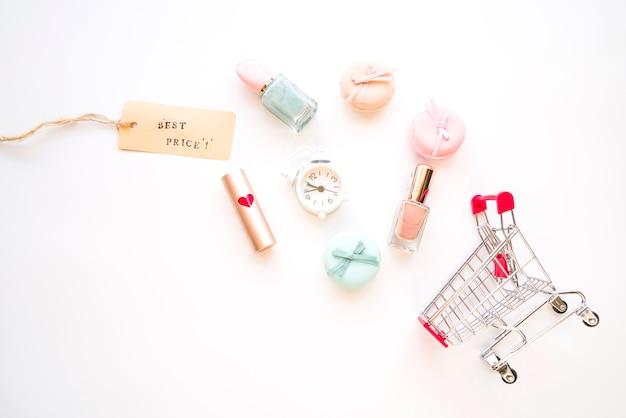 Carrito de compras con reloj despertador pequeño, macarrones, etiqueta de venta, lápiz labial y esmalte de uñas