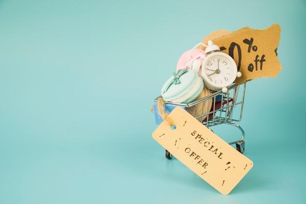 Carrito de compras con reloj despertador, trozos de papel y macarrones cerca de la etiqueta de venta