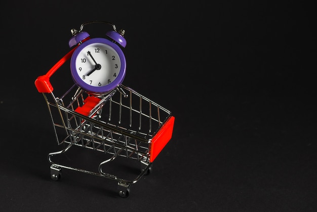 Carrito de compras con reloj despertador.