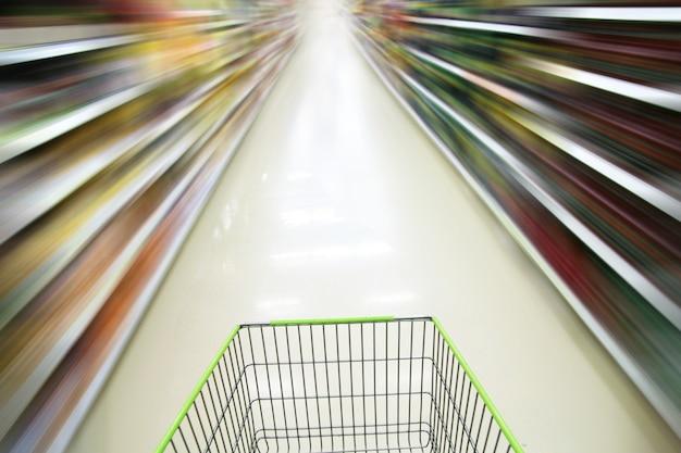 Carrito de compras y supermercado borroso.