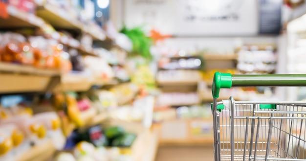 Carrito de compras de supermercado con desenfoque abstracto frutas y verduras frescas orgánicas en los estantes de la tienda de comestibles