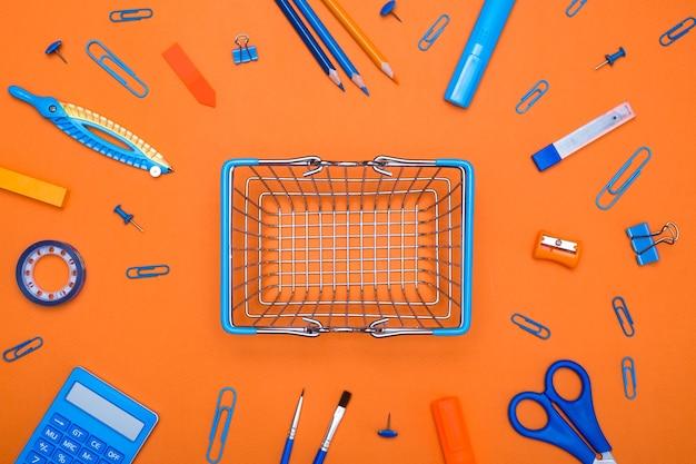 Carrito de compras con útiles escolares sobre fondo naranja