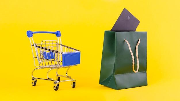 Un carrito de compras vacío cerca de la bolsa de la compra con la tarjeta de viaje contra el fondo amarillo