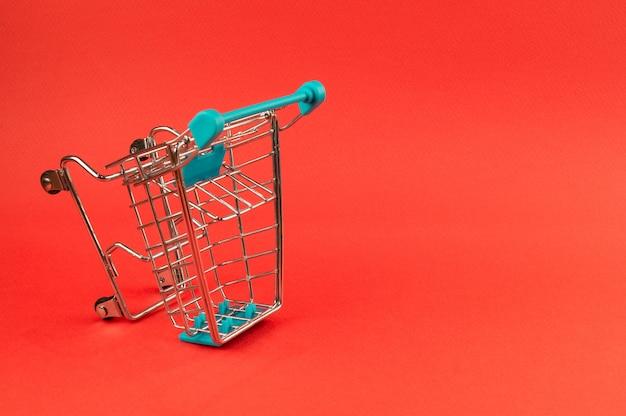 Carrito de compras vacío sobre fondo rojo brillante