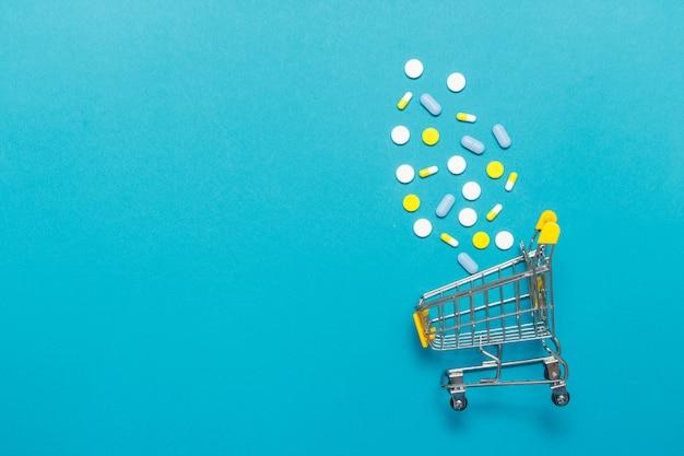 Carrito de compras con una variedad de píldoras de medicina un fondo azul.