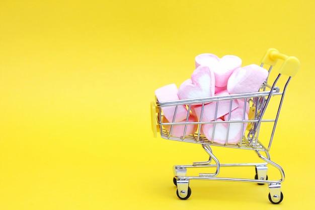 El carrito de juguetes del supermercado está lleno de malvaviscos en forma de corazones.