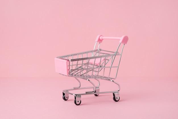 Carrito de mercado de compras pequeño sobre un fondo rosa, espacio de copia, vista lateral del concepto de compras