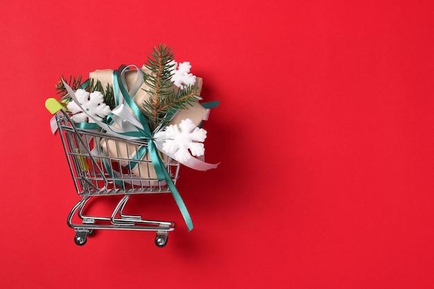 Carrito con regalos de año nuevo en papel kraft con cintas verdes y blancas sobre superficie roja. concepto de compras de navidad. espacio para deseos. tarjeta navideña. vista desde arriba
