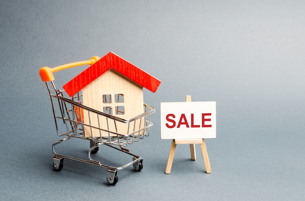 Carrito de supermercado con casas y un cartel de venta.