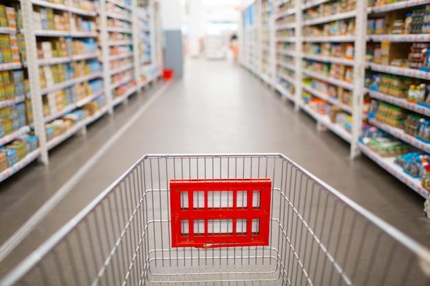 Carrito de supermercado y estanterías con productos en la tienda.