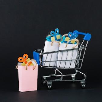 Carrito de supermercado de juguete con regalos en paquetes.