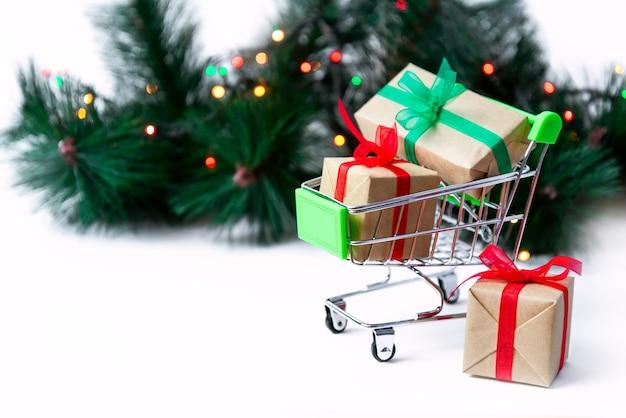 Carrito de supermercado pequeño con cajas de regalo en el árbol de navidad con guirnaldas de luces. creativo