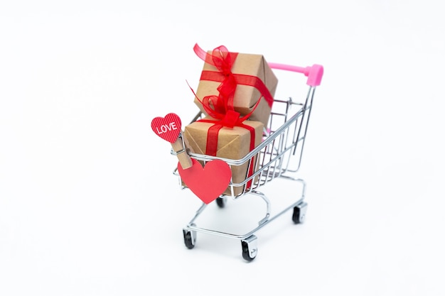 Carrito de supermercado pequeño con cajas de regalo sobre fondo blanco.