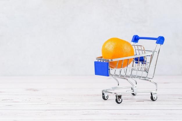 Carrito de supermercado realista, carrito de compras vacío para el comprador, concepto de consumismo, mandarina en carrito