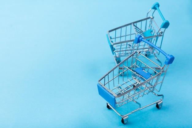 Carritos de compras sobre fondo azul con espacio de copia