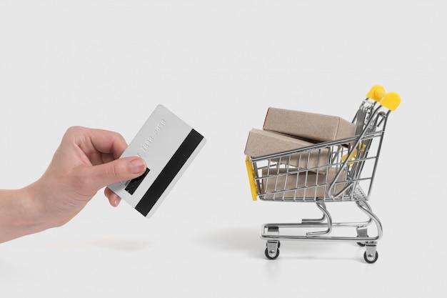 Carro con cajas y mano sujetando una tarjeta de crédito