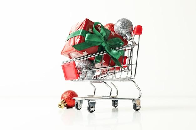 Carro de la compra con caja de navidad y accesorios en mesa blanca
