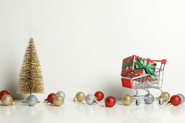 Carro de la compra con caja de regalo y accesorios de navidad en blanco