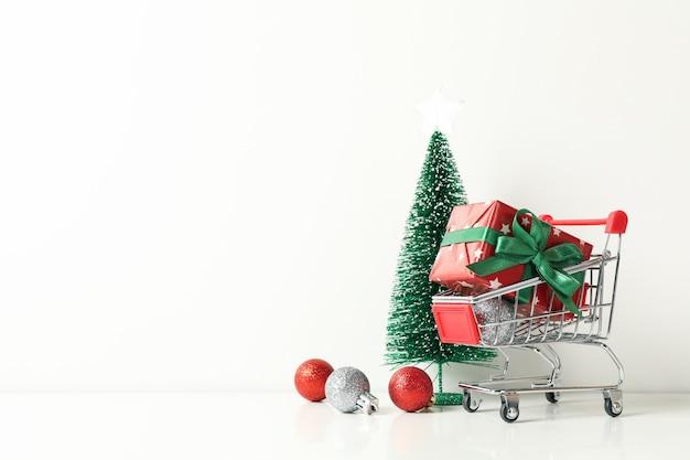 Carro de la compra con caja de regalo y accesorios navideños en mesa blanca