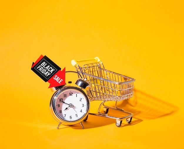 Carro de la compra cerca del reloj de alarma