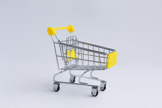 Carro de la compra de comestibles de metal pequeño, sobre un fondo blanco.