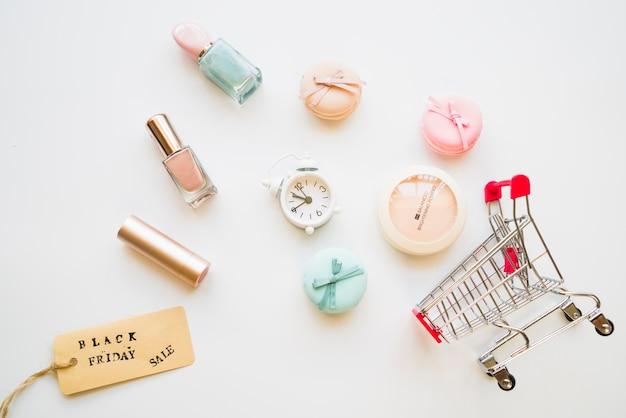Carro de la compra con poco posponer, macarrones, etiqueta de venta y esmalte de uñas