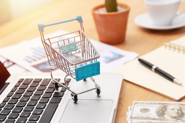 Carro de la compra en el teclado del ordenador portátil, compras en línea