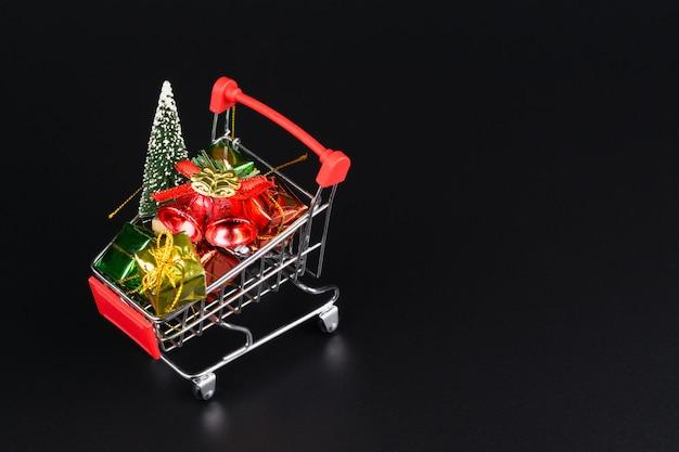 Carro de compras con árbol de navidad y cajas de regalo en miniatura sobre fondo negro