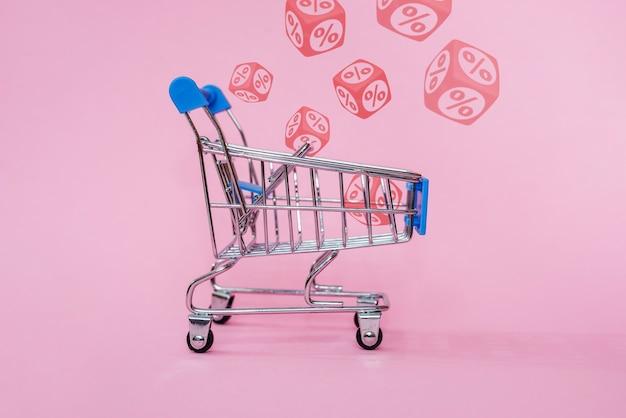 Carro de compras azul con signos de porcentaje rojos en cubos sobre fondo rosa, concepto de venta minorista y descuento