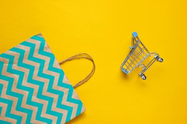Carro de compras y bolsa de papel sobre fondo amarillo. concepto de cliente feliz. compras por internet. tienda en línea. consumismo, estilo de vida