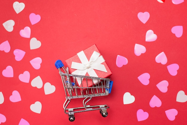 Carro de compras con caja de regalo y corazones para el día de san valentín sobre fondo rojo.
