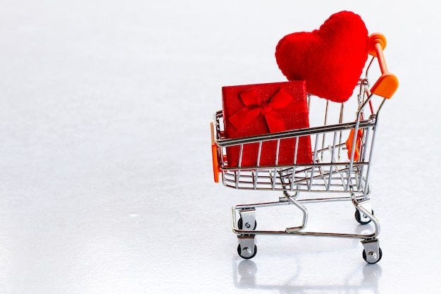 Carro de compras con caja de regalo roja y corazones rojos de confeti sobre un fondo gris copia espacio