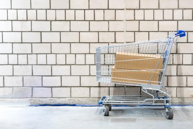 Carro de compras con cajas delante de la pared de ladrillo